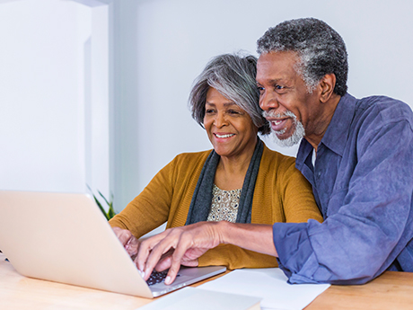 Elderly African-American couple looking at documents on a laptop screen.