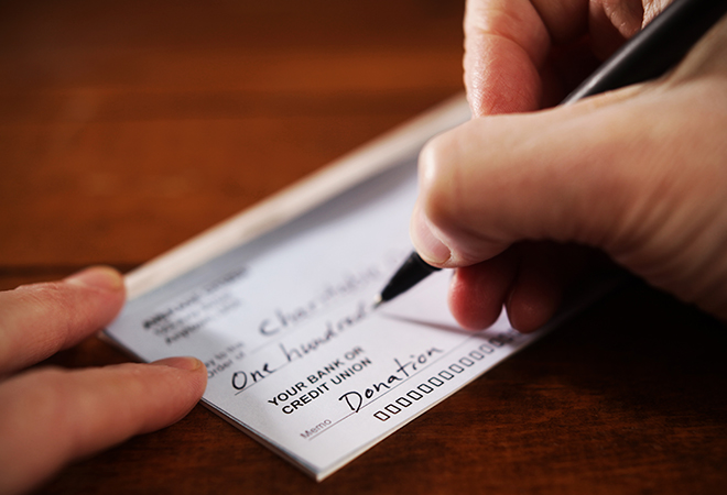 Close up of hand writing a donation check