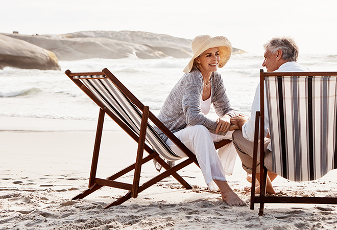 Retired couple sitting on the beach