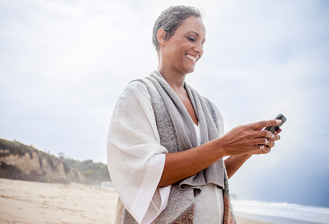 Woman on Beach Looking at Phone