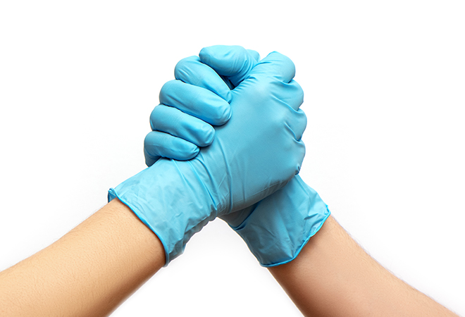 Hands, sleeved in surgical gloves, clasped.