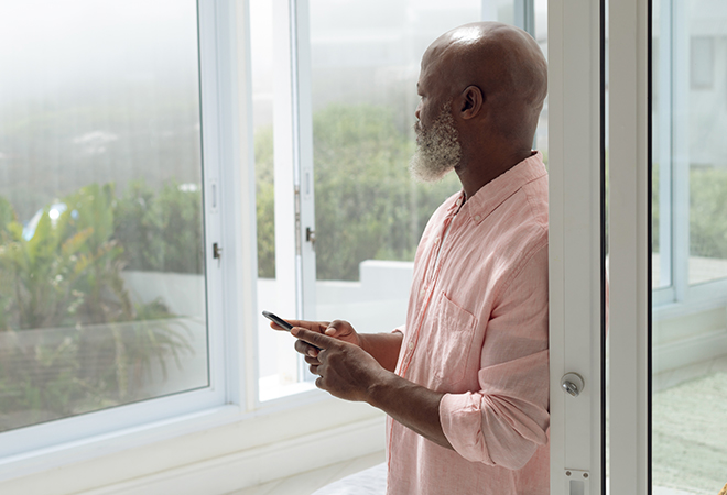African-American male, holding smartphone, looks out past open window.