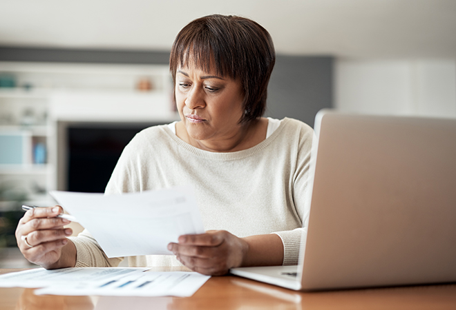African-American woman looking over documents at kitchen table.