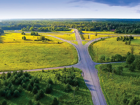 Highway that diverges into three paths surrounded by lush greenery.