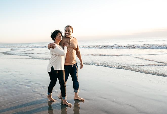 Older African-American couple walking barefoot down beach.