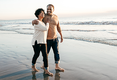 Older African-American couple walking barefoot down beach.