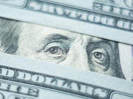 Ben Franklin eyes looking through 100 dollar bills