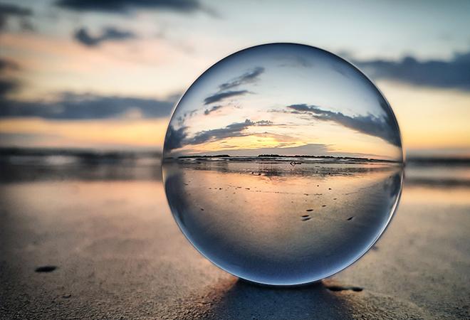 Clear globe sitting on the beach