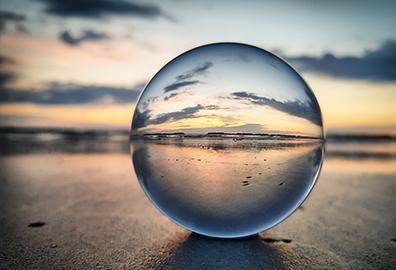 Clear globe sitting on beach