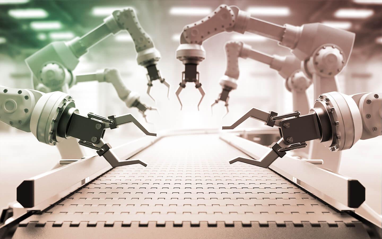 Photograph of various robotic arms over a conveyor belt.