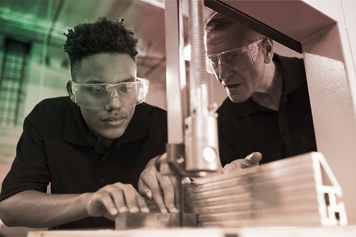 Photograph of older male instructing a younger male on how to use a machine.