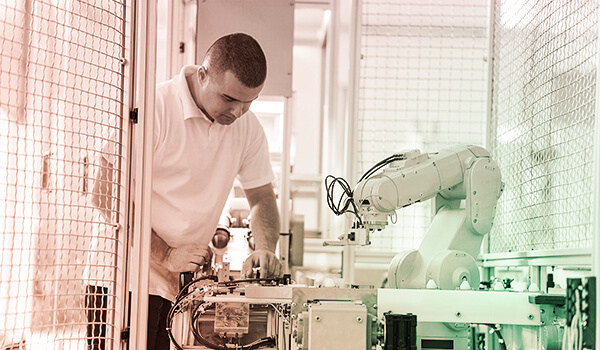Photograph of man working with industrial robotic machine.