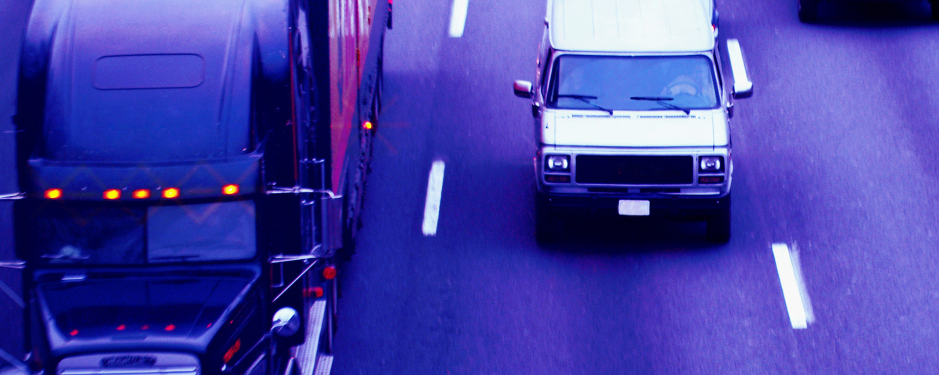Semi-truck and van driving down freeway