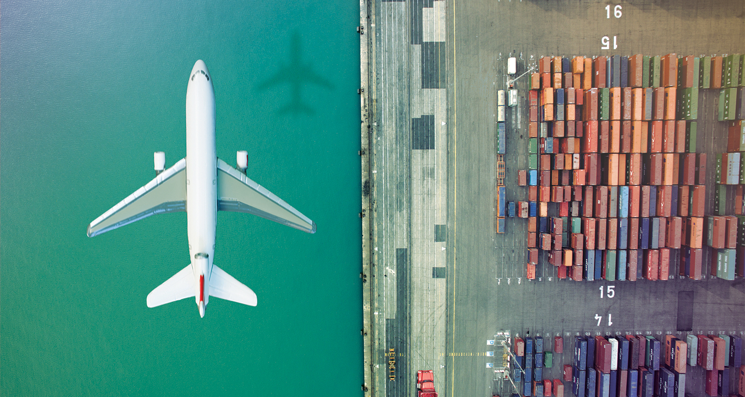 Airplane flying over water next to shipping container yard