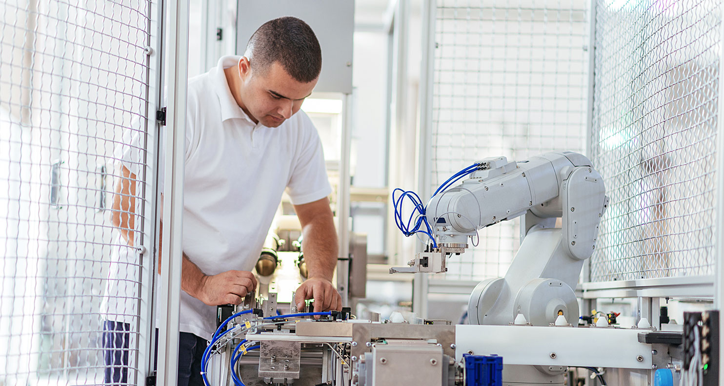 Man working on assembly with a robotic machine