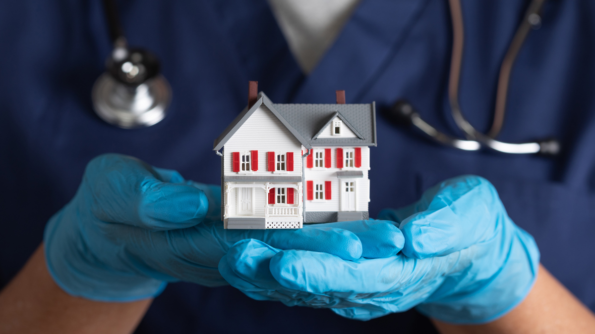 Medical work wearing gloves and holding toy house in hands