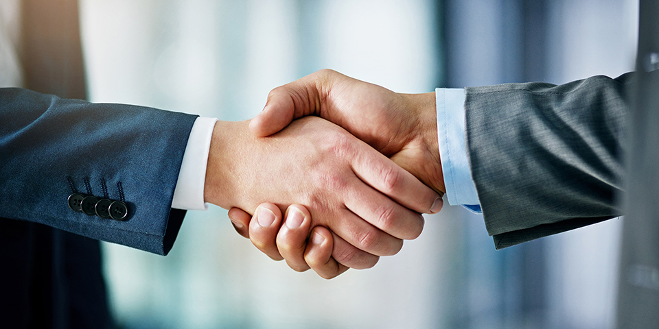 Photo of two hands embraced in a handshake.
