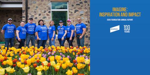 Photo of Baird associates standing in front of garden full of tulips
