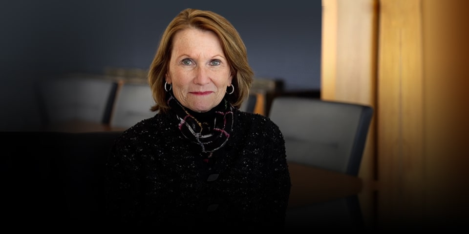 Photo of Mary Ellen Stanek, short light brown hair wearing dark blazer, sitting in empty conference room.