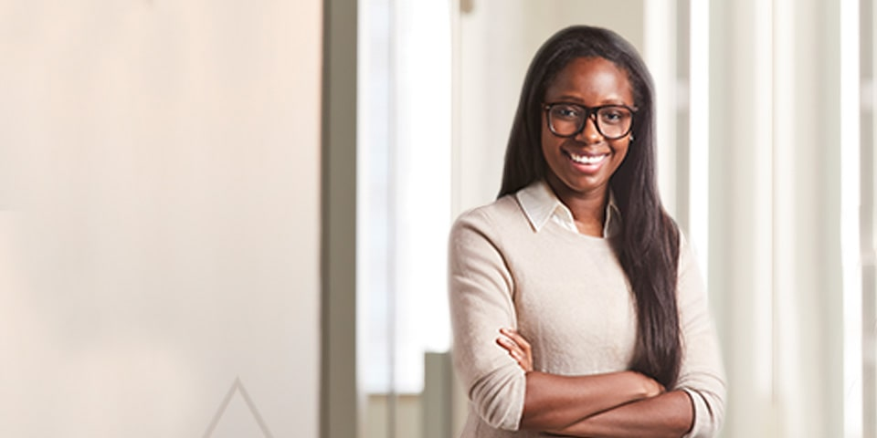 Photo of Nina Essandoh, long bruntter hair and wearing oatmeal colored sweater and glasses, standing in office setting.