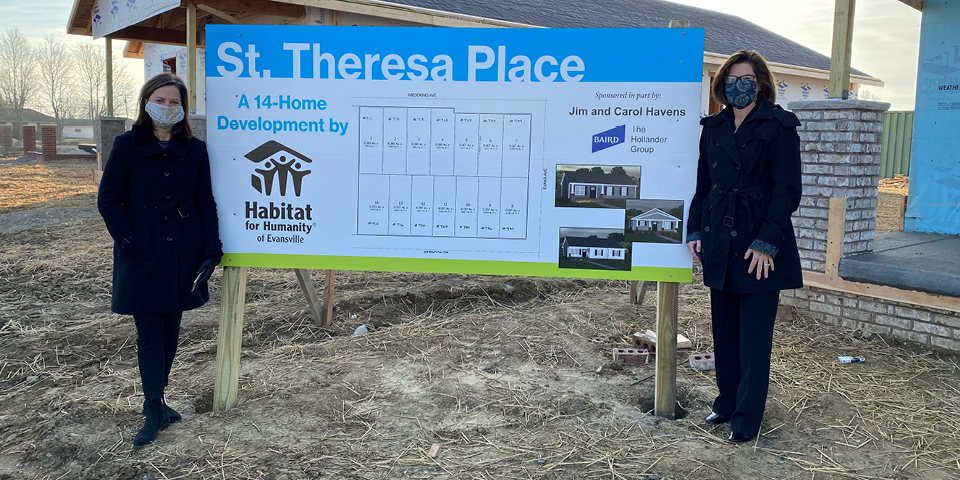 Two associates from The Hollander group posing with a Habitat for HUmanity St. Theresa Place sign outside of the construction area.